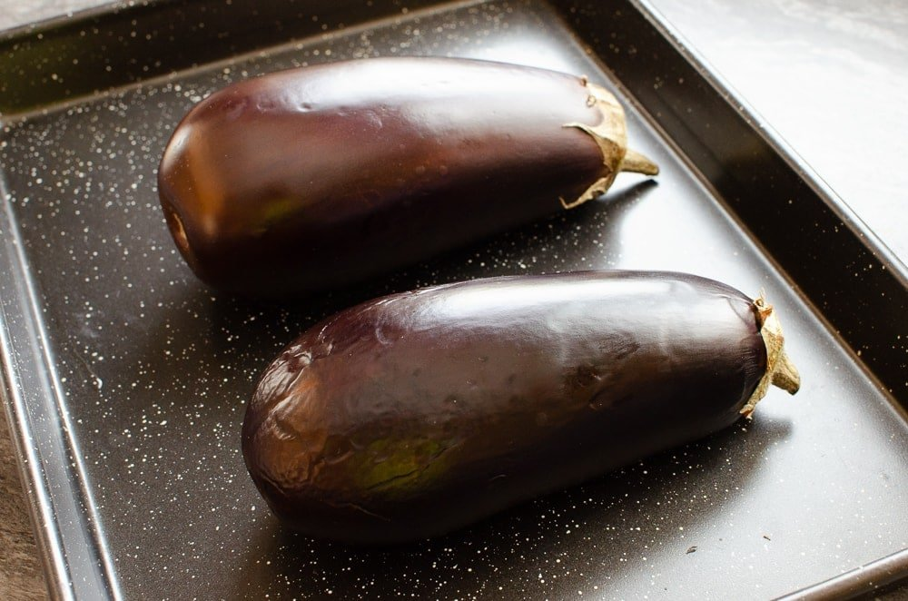Two aubergines(egg plants) on a black baking tray
