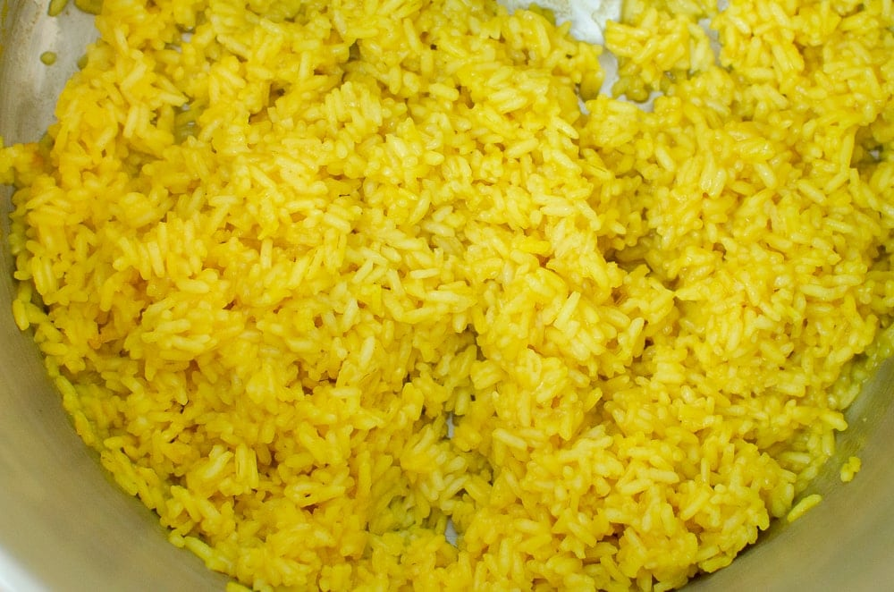 Turmeric rice cooked in a silver pot