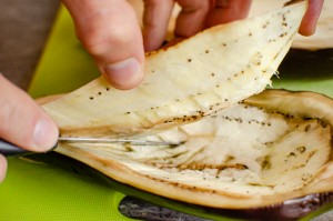 cutting out the inside of a aubergine with am knife on a green chopping board