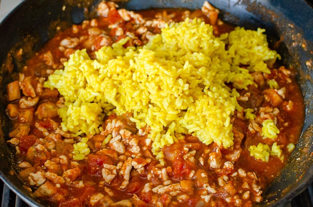 Turmeric rice being added to the turkey mince mixture cooking in a cast iron pan