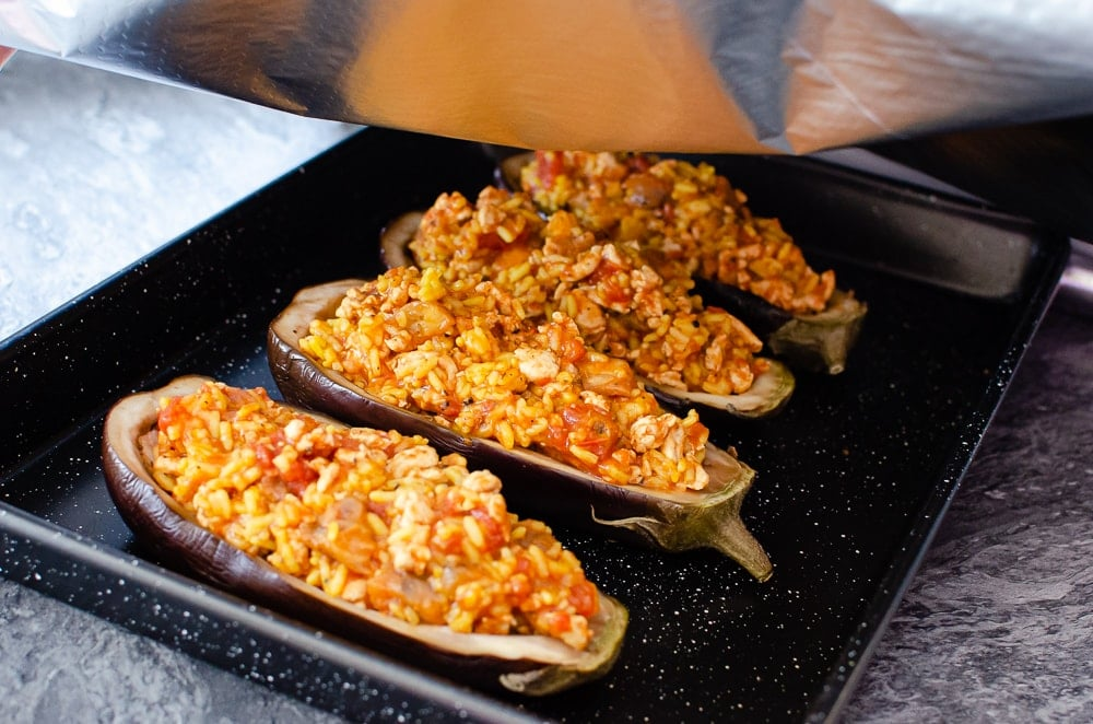 Turkey and Rice Stuffed Aubergine in a black baking tray being covered with silver tinfoil ready to bake in the oven