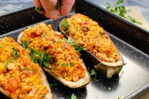 Turkey and Rice Stuffed Aubergine all cooked in a black baking tray and chopped parsley being sprinkled over the top