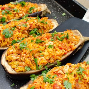 Picking up the stuffed aubergine (egg plant) with a large black spatula