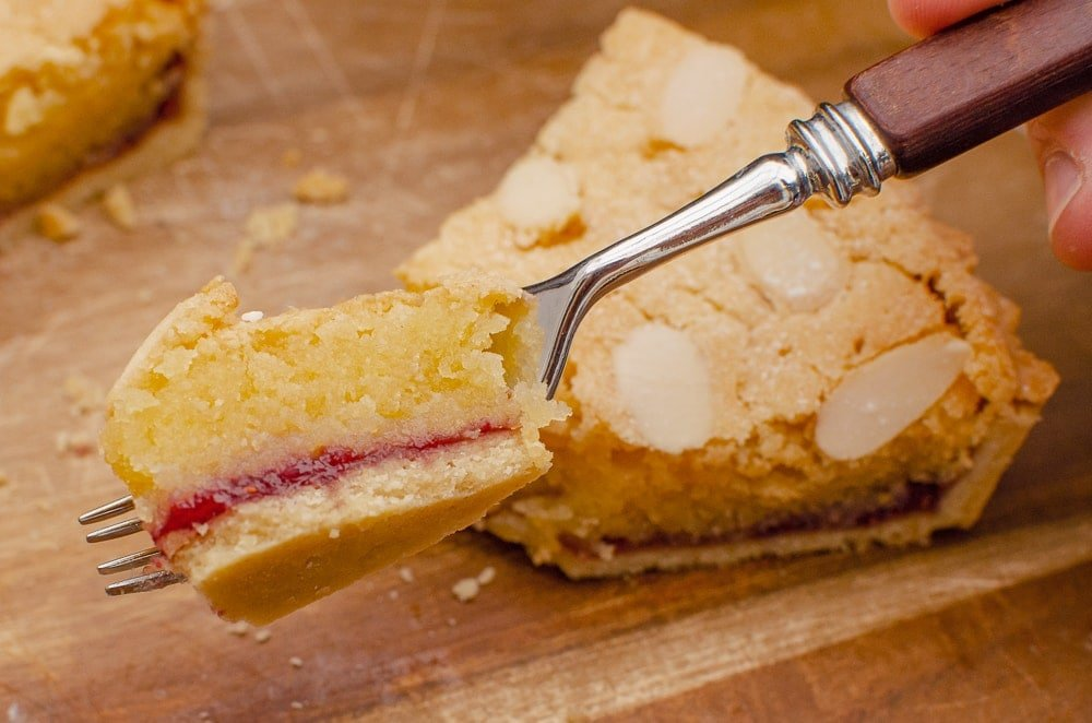 A piece of Bakewell tart on a silver fork showing the layers ready to be eaten