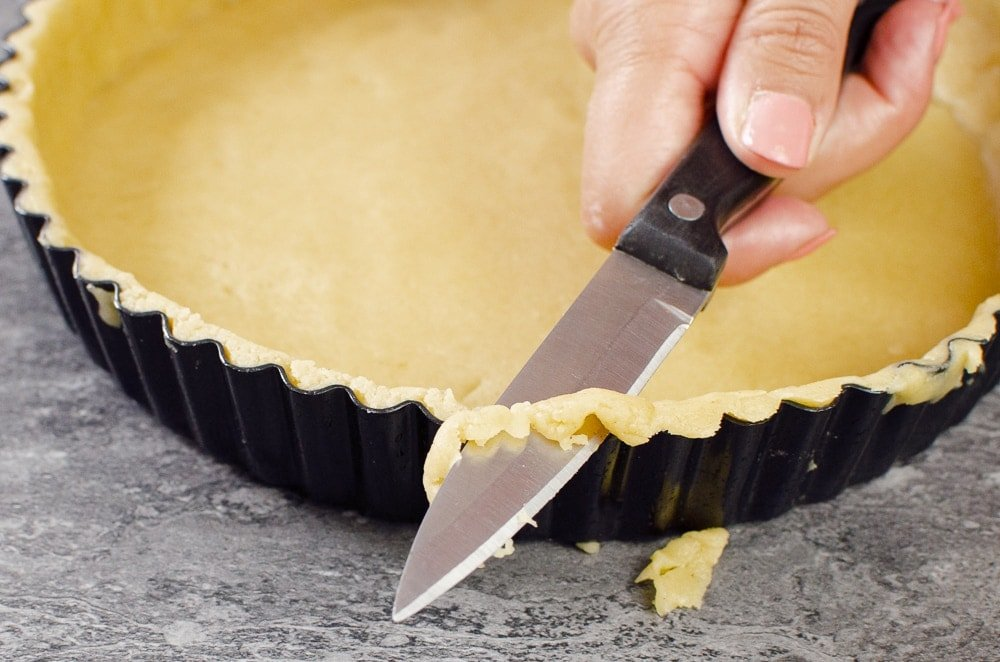 Trimming the short crust pastry edges with a knife from the pastry pan/case