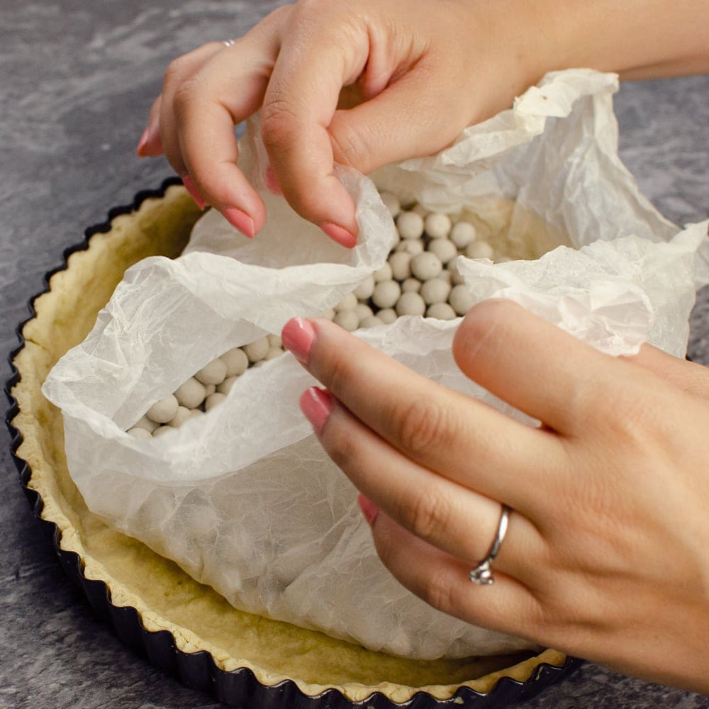 Lifting out the cooking beads with the parchment paper away from the cooked pastry case