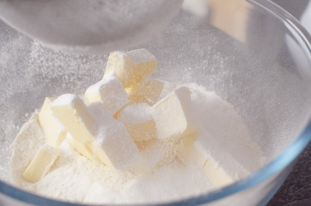 sieving icing sugar onto the butter and sugar in a glass bowl