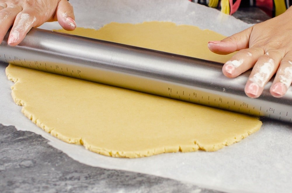 Rolling out pastry with a silver rolling pin on white parchment paper