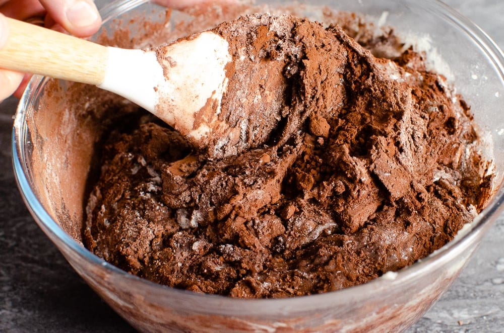 Folding the Chocolate Chip Brownie mix to together with a white spatula