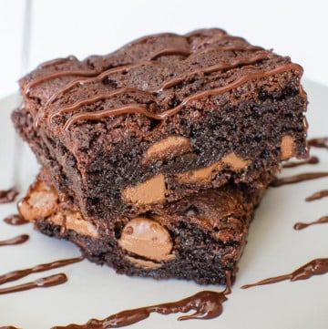 Chunky Chocolate Chip Brownies on a grey plate drizzled with chocolate sauce