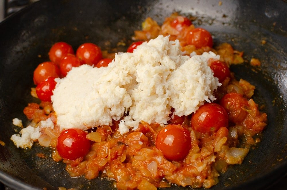 Crab meat added to the chopped onions and cherry tomatoes in a cast iron pan