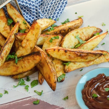 spicy curried potato wedges sprinkled with chopped basil, pouring out of a silver fry basket on white parchment paper with bbq sauce on the side