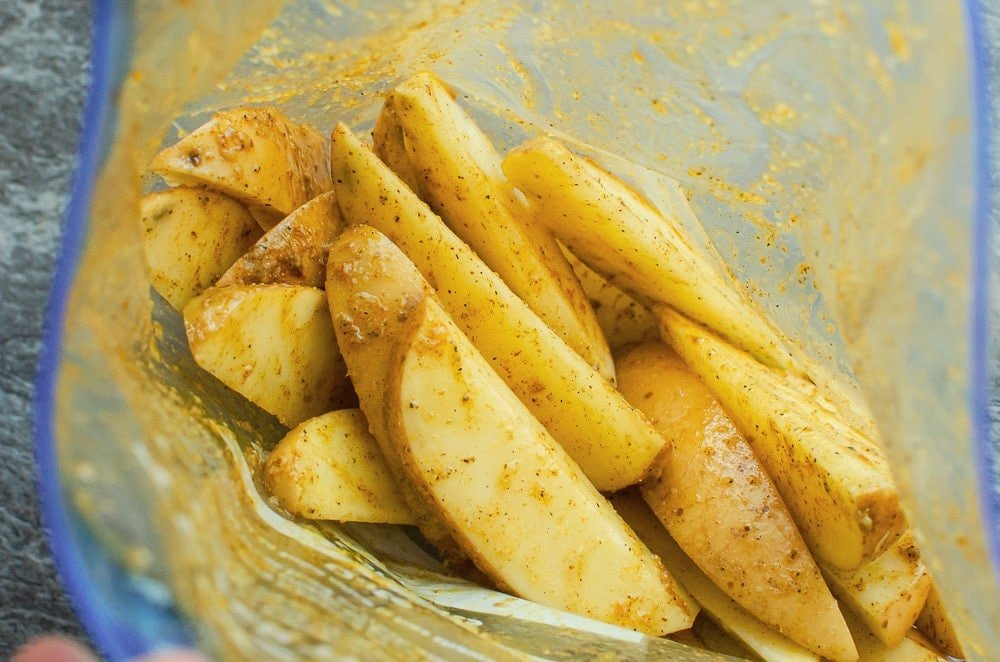 Potato wedges in a sandwich plastic bag being coated in the curry mix