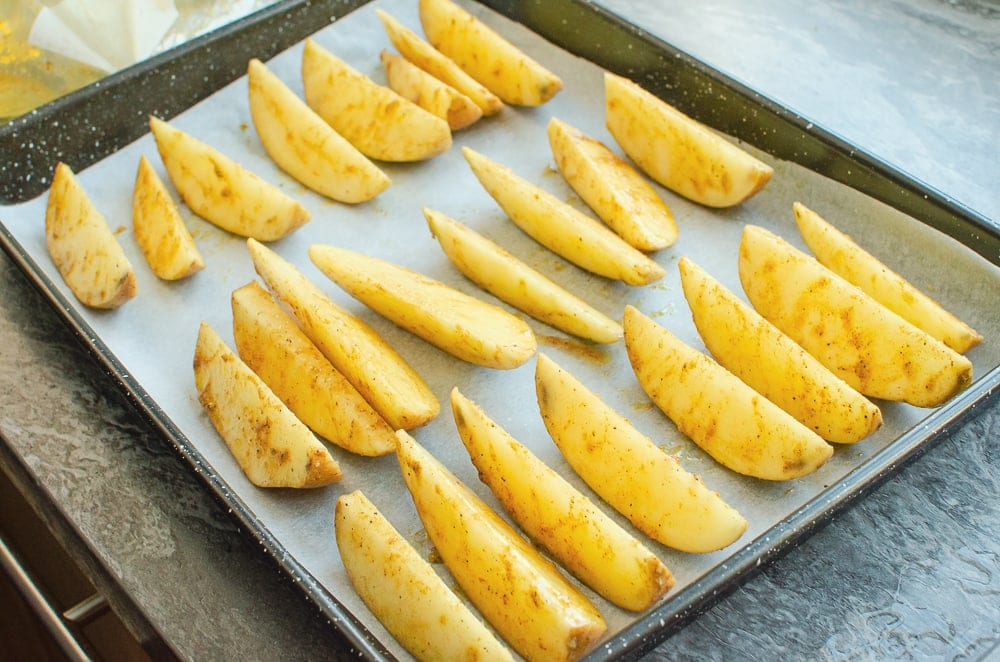 Potato wedges on a baking tray lined with white parchment paper