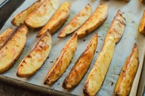 Potato wedges cooked on a baking tray lined with white parchment paper