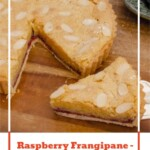 Pinterest image of our Raspberry Frangipane Bakewell Tart on a brown wooden chopping board with a slice being picked up with a silver cake slicer