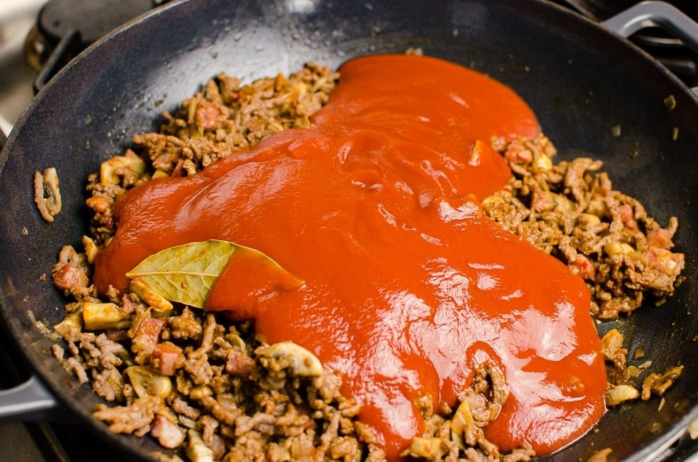 passata, tomato and garlic puree, herbs and bay leaf added to beef mince.