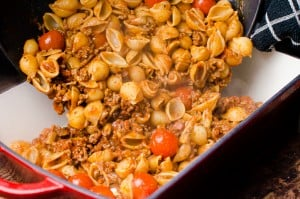 conchiglie pasta shells added to bolognese with cherry tomatoes and tipped into a oven proof dish