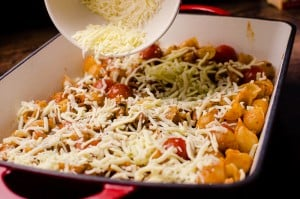 grated chesse being added to bolognese pasta bake in a oven safe dish