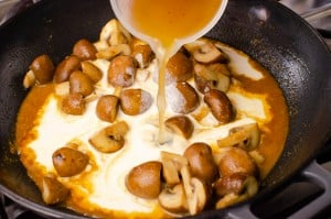 stock being poured into cream and mushrooms in a cast iron dish