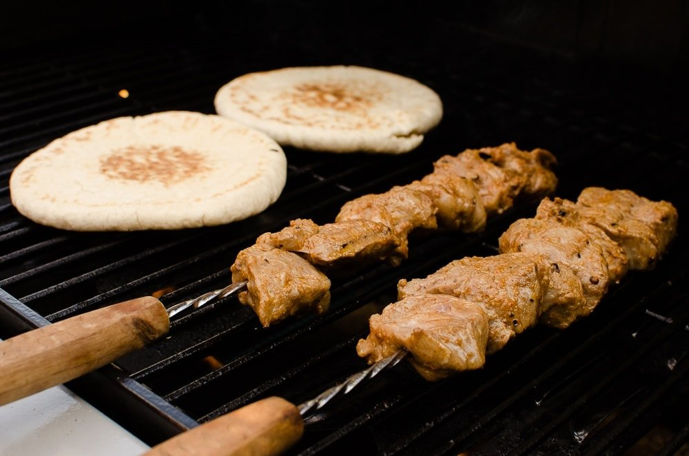 Takeaway Lamb Shish Kebabs being cooked on a gas BBQ with pitta bread
