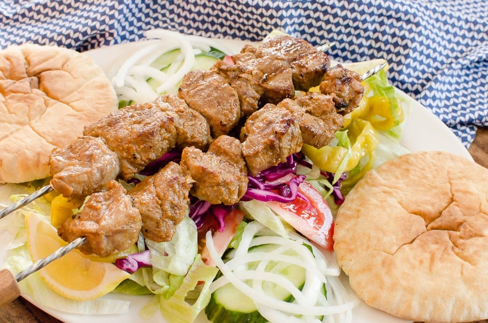 Takeaway Lamb shish kebab served on top of shredded lettuce, red cabbage, cucumber, onion and tomato. Lemon wedges and pitta bread