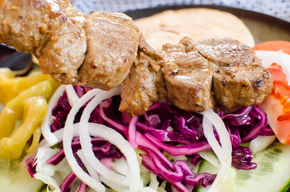 Chunks of lamb served on shredded red cabbage, lettuce, onions, cucumber, tomato and pitta