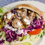 lamb shish kebab served on bed of salad, lettuce shredded cabbage, onion, tomato, cucumber and chillies and garlic mayo sauce.
