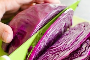 Cutting up red cabbage with a green knife on a green chopping board