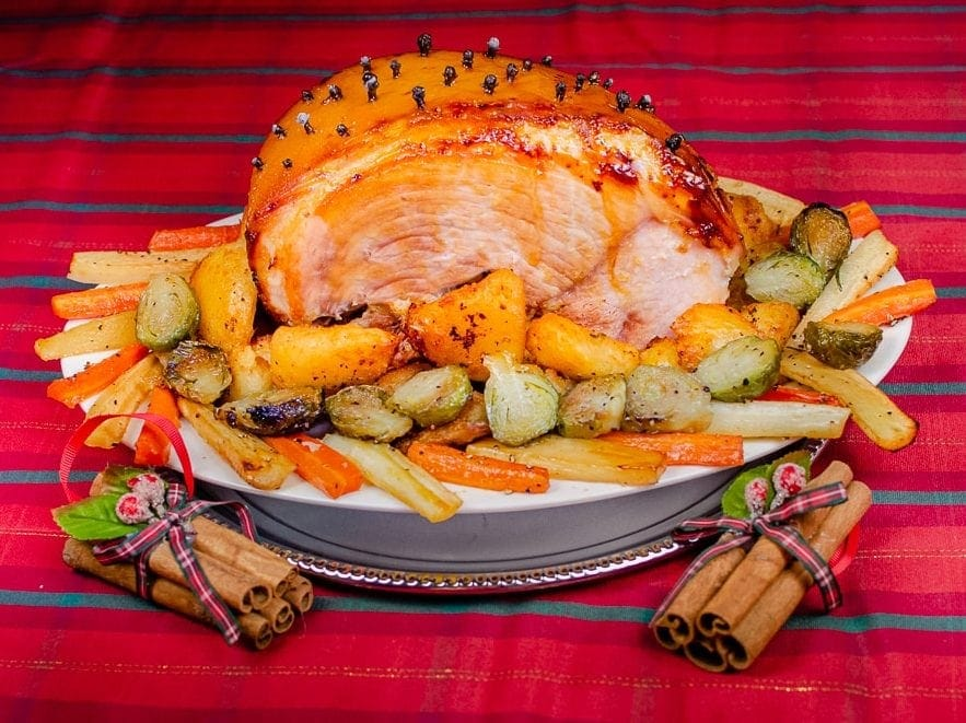 Glazed gammon roast joint with crispy roast potatoes and vegetables served on a white plate on a tartan table cloth