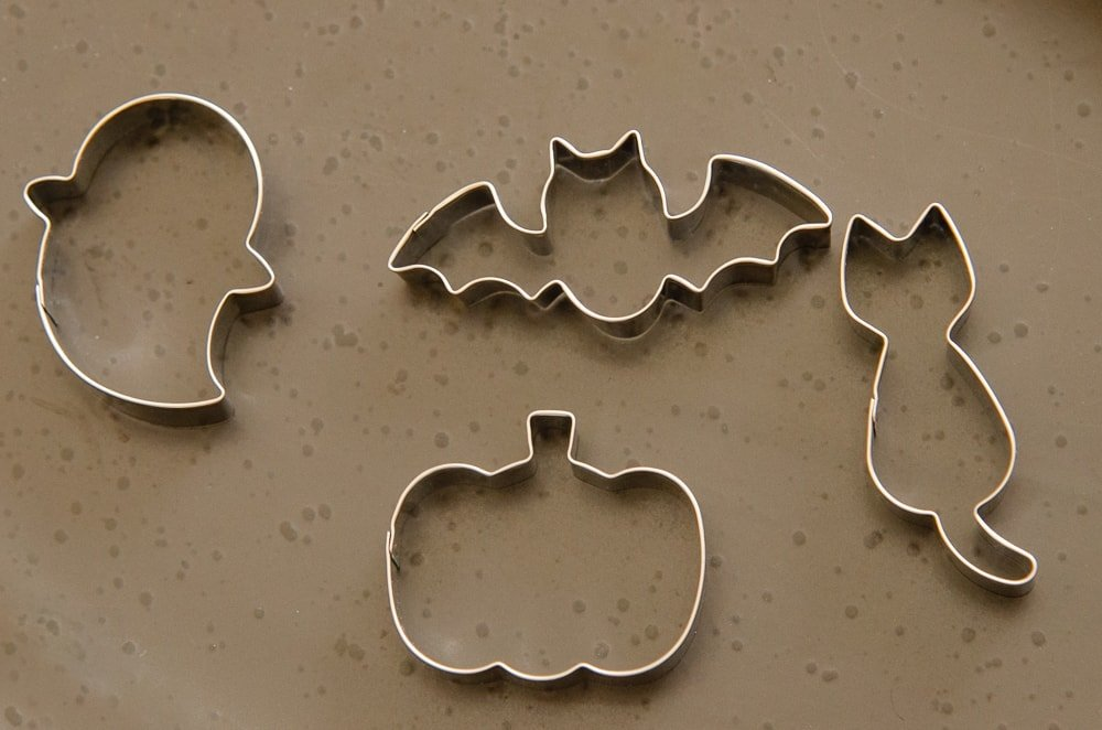Halloween shape cookie cutters of a cat, ghost, bat and a pumpkin