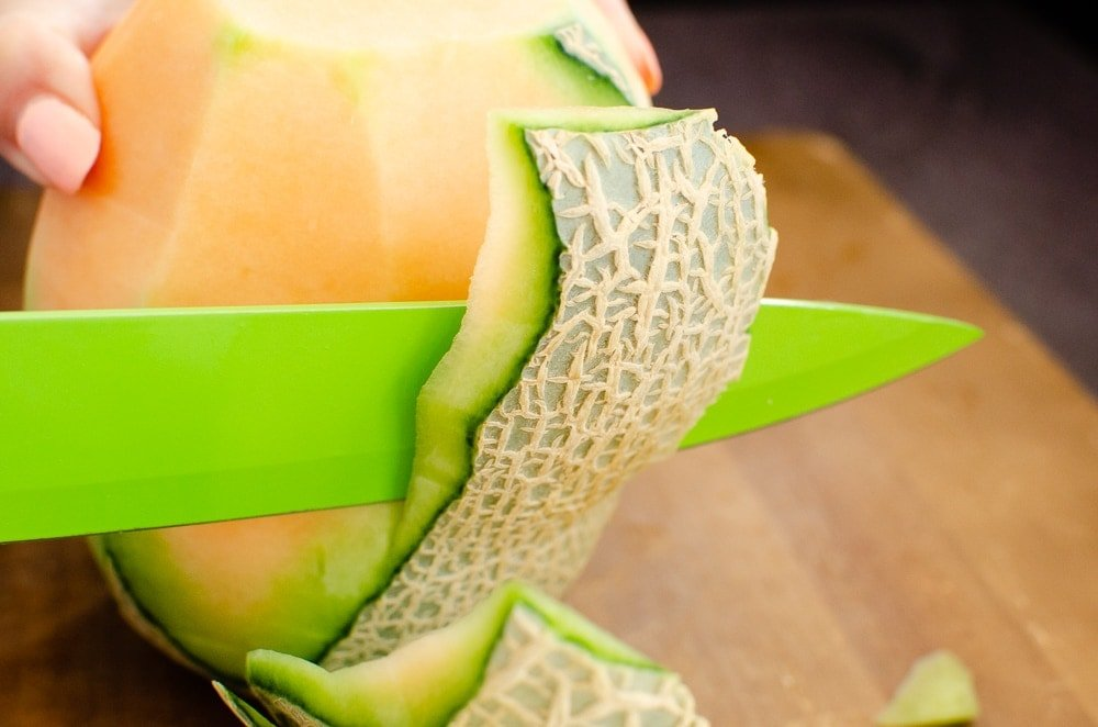 Removing the skin of a cantaloupe melon with a green knife