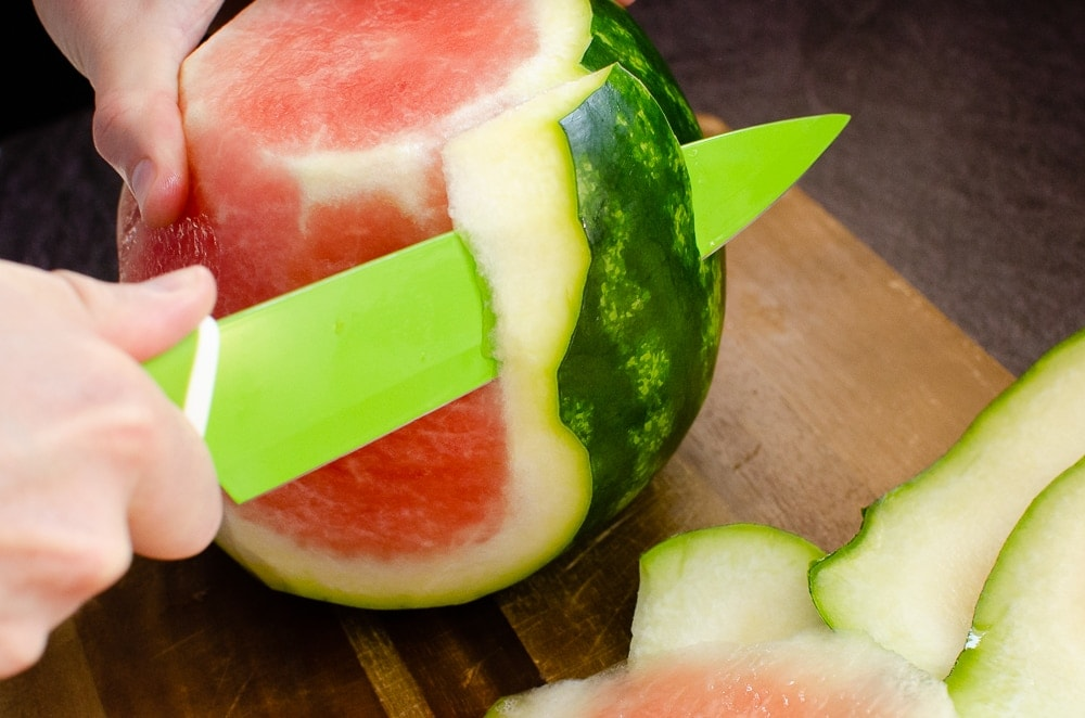 Peeling off the skin of a watermelon with a green knife
