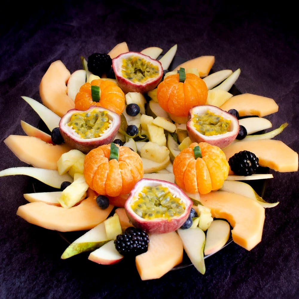 Large black platter plate with slices of cantaloupe melon, clementines,passion fruit,blackberries, pineapple,blackberries, sliced apple