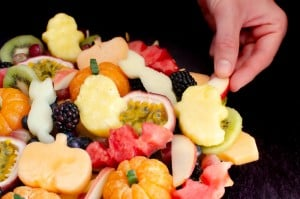 Adding a Halloween cut out shapes of cats,pumpkins,bats and ghosts onto our fruit salad on a black platter plate