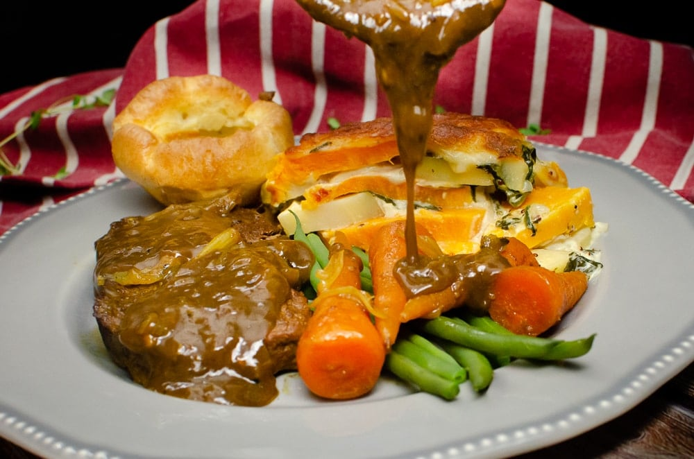 Pouring the Horseradish Gravy over the braising steak served with sweet potato and parsnip gratin, flawless Yorkshire pudding, carrots and green beans