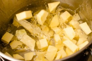 Placing the cubed swede into water in a silver pot to cook