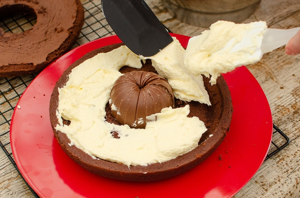 Placing the cream filling around the terry's chocolate orange and in the middle of the chocolate cake on a red plate