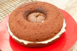 The othe half of the choclate cake has been placed on top of the the cream filling, chocolate orange and bottom cake base