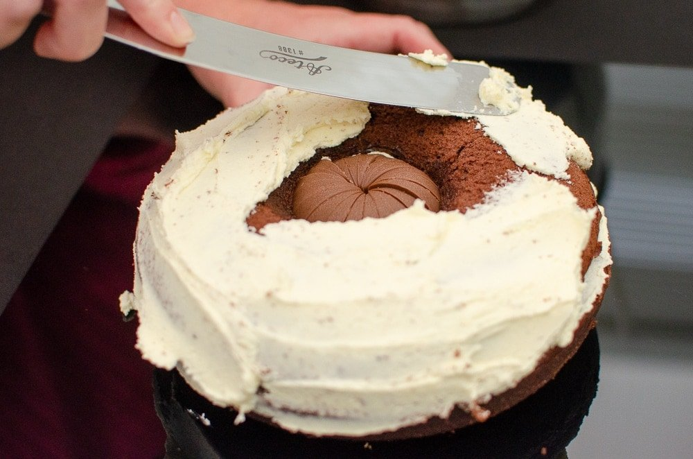 Spreading cream mixture over the chocolate cake with a silver palate knife