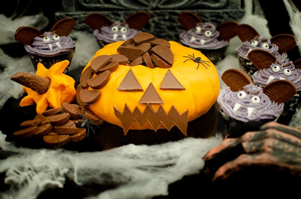 Pumpkin shaped cake with Chocolate Orange-Halloween party idea surrounded with vampire cupcakes and cobwebs