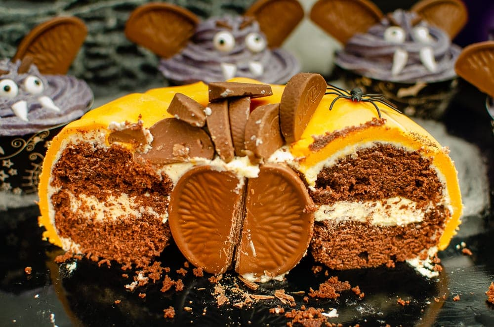 Pumpkin shaped cake with Chocolate Orange-Halloween party idea cut in half showing chocolate and cream layers and a ball of chocolate orange in the middle