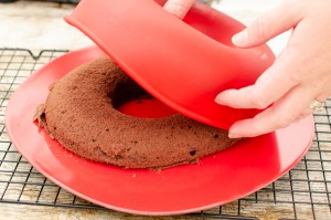 Pushing out the chocolate cake out of the red rubber mould onto a black wire rack