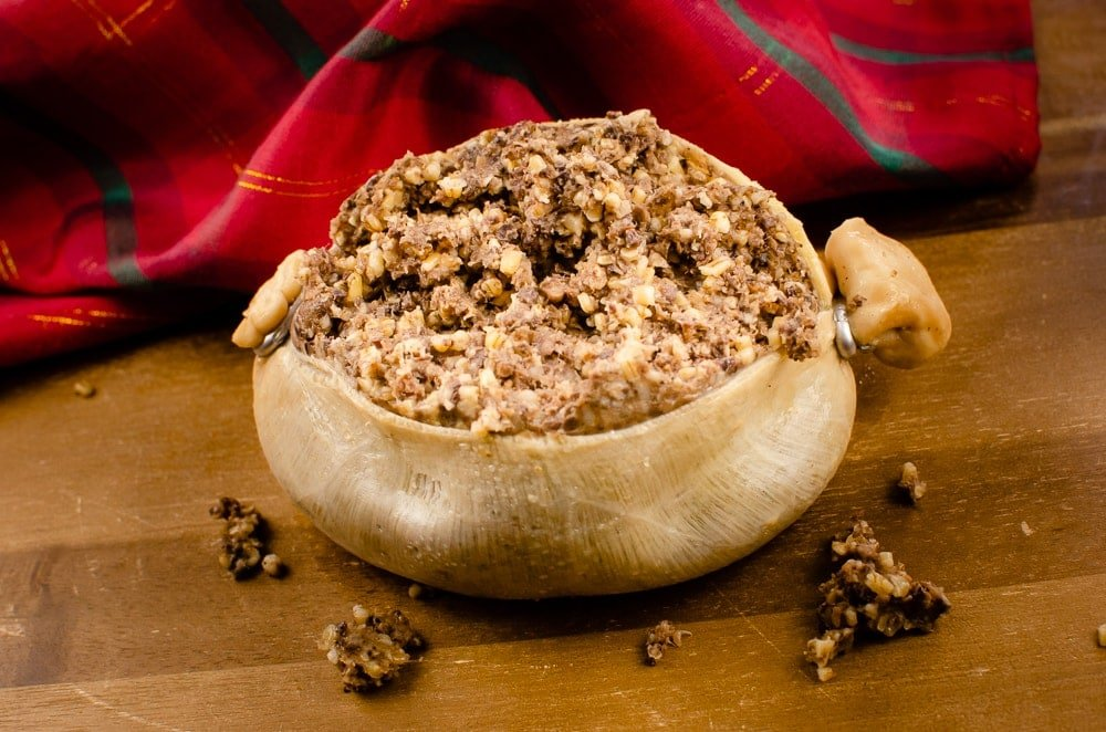 Haggis on a wooden chopping board with a red and green tartan sheet in the back ground