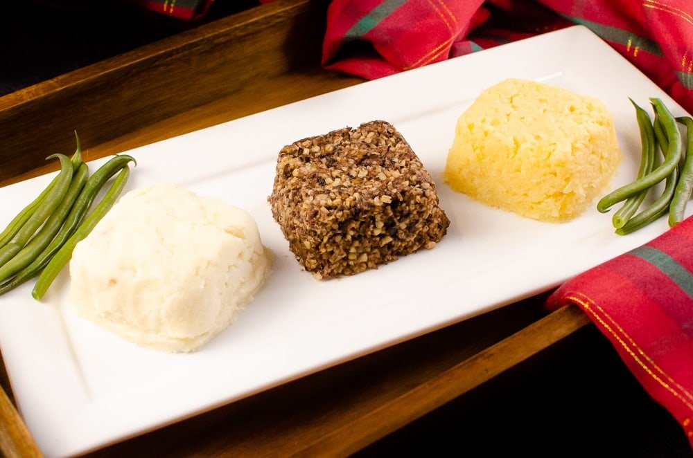 Haggis, Neeps and Tatties served with green beans on a white plate