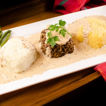 Haggis, Neeps and Tatties with Creamy Whisky Sauce served with green beans on a white plate and a red and green tartan sheet in the background