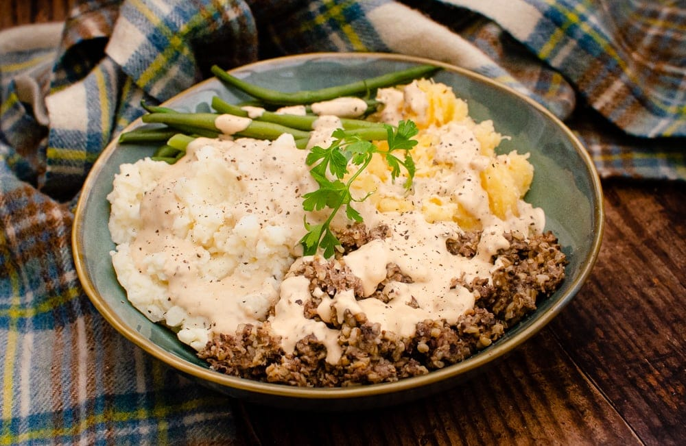 Haggis, Neeps and Tatties with Creamy Whisky Sauce served with green beans and garnished with black pepper and sprig of parsley in a blue bowl and blue and yellow tartan sheet in the background