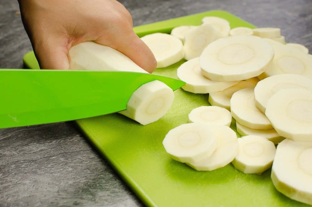 Cutting parsnip into slices on a green chopping board with a green knife