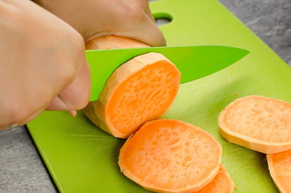 Cutting sweet potato into slices on a green chopping board with a green knife
