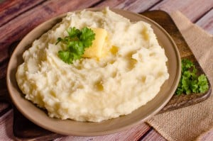 Flawless Mashed Potatoes- Easy Side Dish Recipe served in a brown bowl with butter and parsley on top